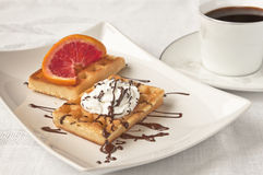 Coffee and waffles with whipped cream. A sweet moment - cup of black coffee and two waffles with whipped cream, chocolate and a slice of red orange on white Stock Photo