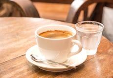 Coffee,White Coffee Mug,Glass water,Wooden table. Stock Photo