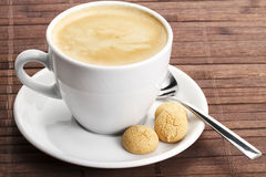 Coffee in a white cup with amarettini and spoon Royalty Free Stock Photos