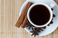 Coffee in a white cup with anise and cinnamon sticks on a bamboo background.  Royalty Free Stock Photography
