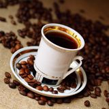 Coffee in white cup. On burlap background Stock Photos