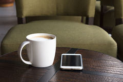 Coffee. A white cup of cappuccino coffee on a table with smart mobile in the coffee shop Stock Photos