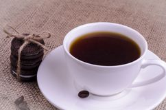 Coffee in a white cup with cookies, coffee beans and cinnamon stick.  royalty free stock photography