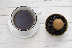 Coffee in white cup with an egg and coffee beans. Top view Royalty Free Stock Image