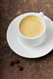 Coffee in a white cup with grains. Coffee in a white cup on a brown surface Royalty Free Stock Photo