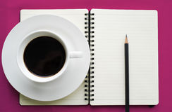 Coffee in white cup with Journal book and pencil Royalty Free Stock Photo