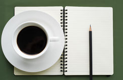Coffee in white cup with Journal book and pencil Stock Photo