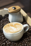 Coffee. White cup of latte art coffee on coffee beans Royalty Free Stock Image