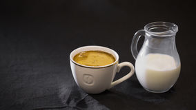 Coffee in a white Cup milk in a small jug on black background Stock Photography