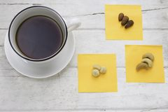 Coffee with white cup and mixed nuts on white table. Top view Royalty Free Stock Image