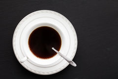 Coffee in white cup and placed on black stone plate Stock Photos