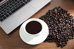 Coffee in white cup and see the Computers,Coffee beans Nearby. Royalty Free Stock Images