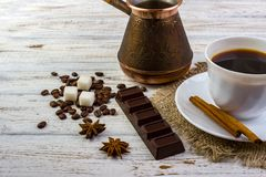 Coffee in a white cup on a small plate on sacking and cinnamon sticks. Coffee beans, pieces of sugar, anise and a chocolate bar on Stock Photo