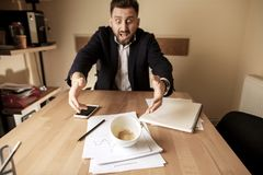 Coffee in white cup spilling on the table in the morning working day at office table. The businessman and coffee in white cup spilling in slow motion or movement Stock Image