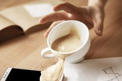 Coffee in white cup spilling on the table in the morning working day at office table. The male hands and coffee in white cup spilling in slow motion or movement Royalty Free Stock Photo