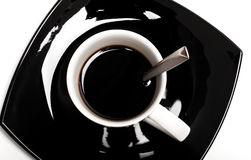 Coffee in white cup with spoon on black saucer Stock Photo