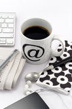 Coffee in white cup with at symbol. Mobile, headphones, newspaper, napkin, teaspoon and keyboard stock image