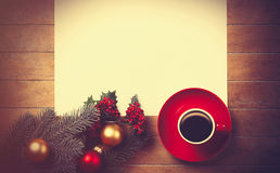 Coffee and white paper near branch with christmas toys Royalty Free Stock Image