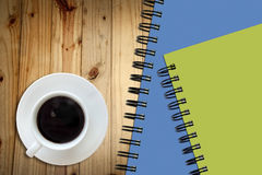 Coffee and white sketch book on wood ta. White cup of hot coffee and white sketch book on wood table Royalty Free Stock Photography
