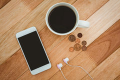 Coffee and white smartphone with white headphones Royalty Free Stock Images