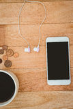 Coffee and white smartphone with white headphones Royalty Free Stock Photography