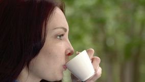 Coffee by the window. Woman drinking coffee by the window in rainy weather stock footage