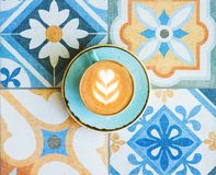 Free Coffee With Latte Art In Blue Cup On Colorful Tile Background. Royalty Free Stock Photos - 153957858