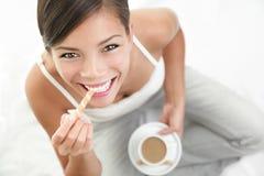 Coffee woman. Coffee anc cookie woman. Beautiful Asian / Caucasian woman enjoying coffee with a cookie Stock Image