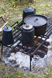 Coffee on Wood Campfire Cooking, Camp, Camping. Coffee is being kept warm in the pots as the sit over the campfire. Old time vintage type pots and pans are being Stock Photos