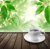 Coffee on wood floor with green bokeh . Stock Image