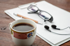 Coffee on wood table.  Pen, headphones and glasses in background Royalty Free Stock Photo
