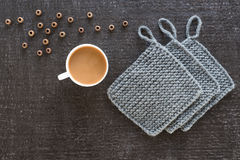 Coffee, wooden beads and knitted props on black. Cup of coffee, wooden beads and grey knitted props on a black background Stock Images