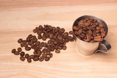 Coffee on wooden board. Coffee beans in cup & on wooden top Stock Image
