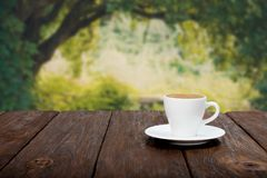 Coffee on wooden table with beautiful forrest background Stock Photography