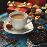 Coffee on wooden table with chocolate sweets and gift box. Cup of coffee close up on a wooden table with a variety of chocolate sweets and gift box Royalty Free Stock Photography