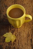 Coffee on wooden table decorated with autumn leaf Royalty Free Stock Photo