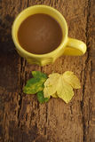 Coffee on wooden table decorated with autumn leafs Stock Images