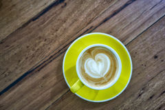 Coffee on wooden table. Coffee in yellow mug and plate with heart shaped coffee art on wooden table stock image