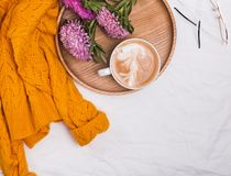 Coffee on wooden tray, flowers and yellow knitted sweater. On wooden tray, flowers and yellow knitted sweater, top view royalty free stock photo