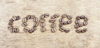 Coffee word made of beans on grunge wooden surface Stock Photography