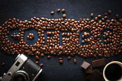 Coffee word made by coffee beans with camera  chocolate and cup of coffee Royalty Free Stock Photo