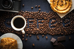 Coffee word made by coffee beans with camera  chocolate , pastry and cup of coffee Royalty Free Stock Image