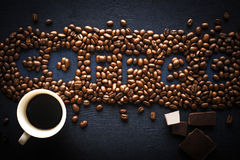 Coffee word made by coffee beans with chocolate and cup of coffee Stock Photos