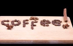 Coffee word written with beans and cinnamon and anise. On a wooden surface Stock Photo