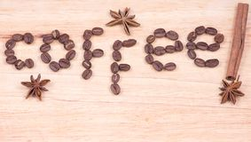 Coffee word written with beans and cinnamon. And anise on a wooden surface Royalty Free Stock Photo