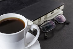 Coffee while working. Diary with glasses lying on the sidelines. Coffee break Royalty Free Stock Image