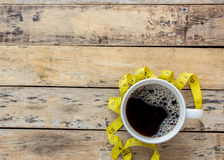 Coffee and yellow measuring tape on wooden table Stock Photography