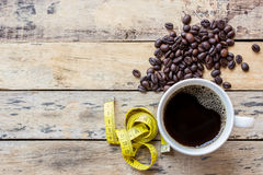 Coffee and yellow measuring tape on wooden table Stock Photo