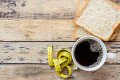 Coffee and yellow measuring tape on wooden table Royalty Free Stock Image