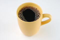 Coffee in yellow mug Stock Images